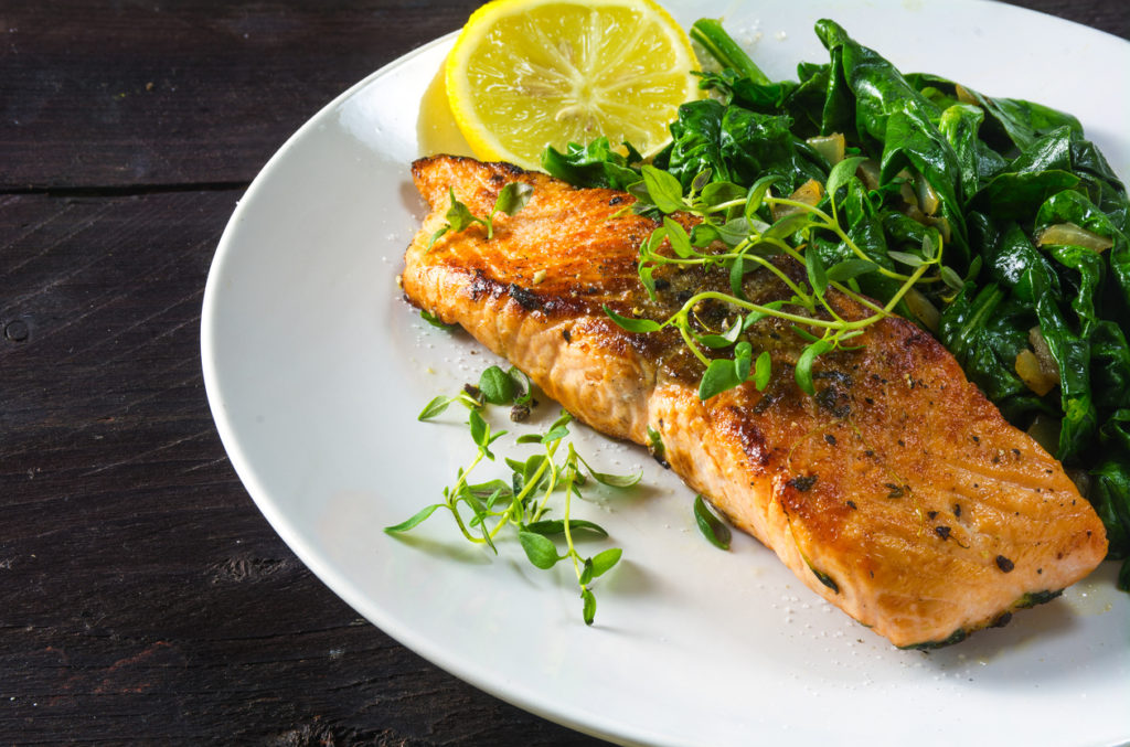 grilled salmon with thyme, lemon and spinach on a white plate on a dark rustic wooden table, homemade vegetarian low carb dish